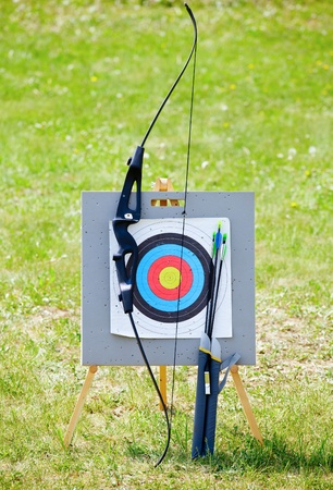 Bow and arrows with archery target outdoors photo