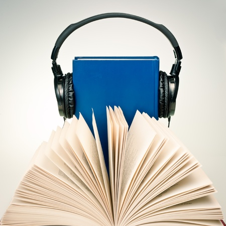 Open book with HI-Fi headphones on a blue book at background photo