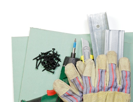 Plasterboard tools set with metal studs, screws, screwgun, cutter and protective gloves on white background photo