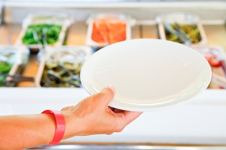 party tray: Hand wearing all-inclusive bracelet holding empty plate against vegetarian buffet table Stock Photo