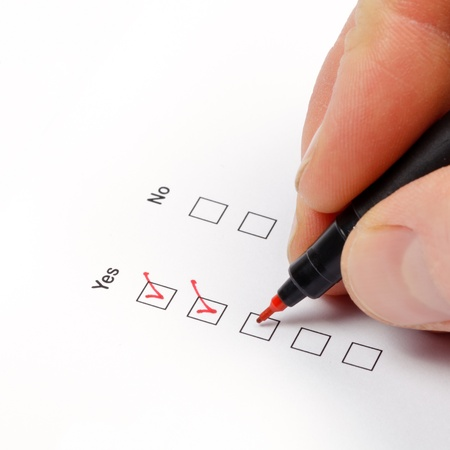poll: Hand with pen over blank check box Yes in application form Stock Photo