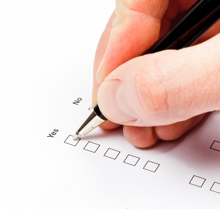Hand with pen over blank check boxes in a form photo