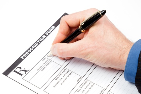 Hand with pen over blank veterinarian prescription form Stock Photo