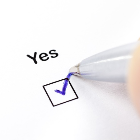 Hand with pen marks the check box Yes Stock Photo - 11475865