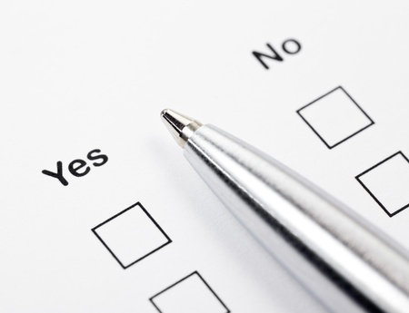 tickbox: Close up shot of ballpoint between unfilled tick boxes Yes and No