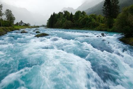 Milky blue glacial water of Briksdal River in Norway