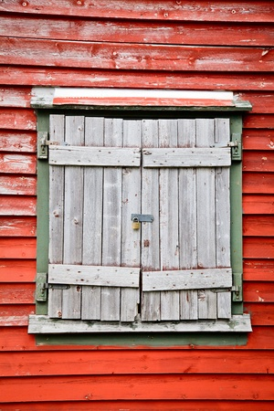 keylock: Old weathered wooden shuttered window on a red wall locked