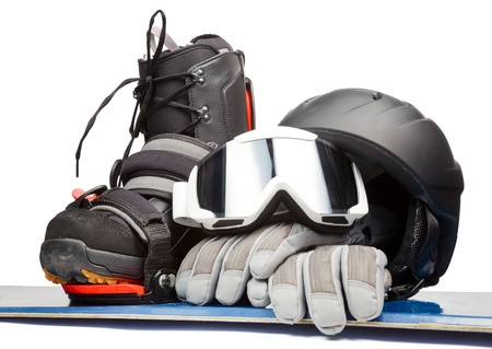 Snowboard with boot helmet gloves and goggles on white background
