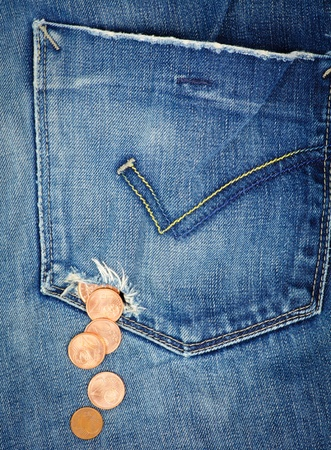 deprivation: Money fall out from a hole in jeans pocket