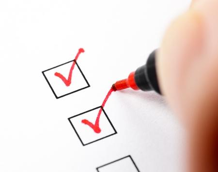Main avec stylo rouge marquant une case à cocher Banque d'images