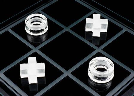 Glass tic-tac-toe game on black background photo