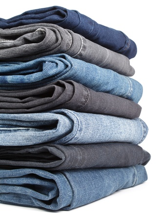 Stack of blue and black Jeans on white background photo