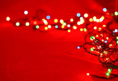 christmas illuminations: Christmas lights on red background, shallow focus Stock Photo