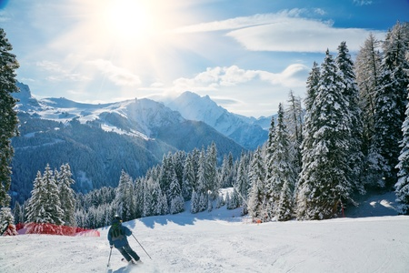 Skier going down the slope at Val Di Fassa ski area in Italy photo