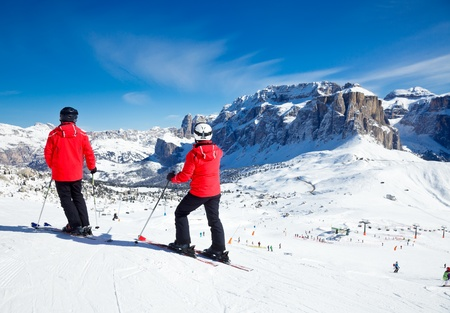 val: Skiers overlooking the piste at Val Di Fassa ski resort in Italy