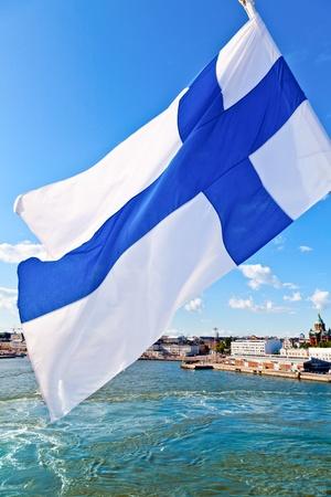 finland: Flag of Finland against Helsinki cityscape