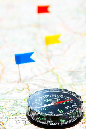Compass on a map with color flag pins in background photo