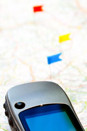 GPS navigator on a map with color flag pins in background photo