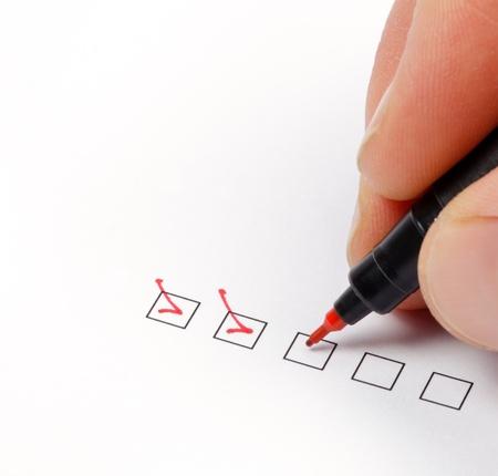 Hand mit roten Stift markieren Sie die Checkbox