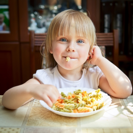 child food: Cute little girl eating Fusilli Stock Photo