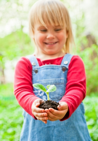 Little girl holding seeding with ground Stock Photo