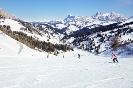 Skiers going down the slope at Sella Ronda ski route in Italy photo