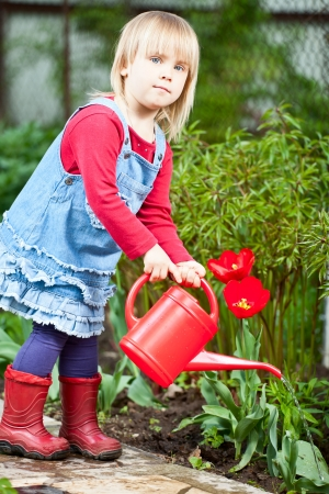 Little girl watering red tulip with red watering can Stock Photo - 13943069