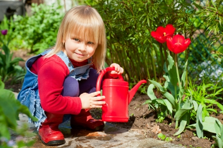 Kleines Mädchen posiert mit roten Gießkanne
