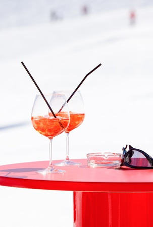 ski run: Champagne cocktails on a red table at Italian ski resort Stock Photo