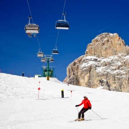 Skier going down the slope under ski lift at Sella Ronda ski route in Italy photo