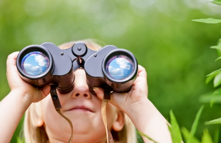girl scout: Little girl looking through binoculars outdoors Stock Photo