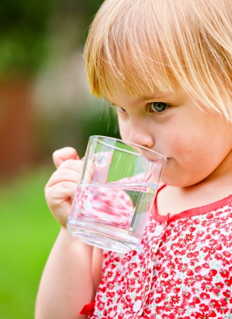 Cute little girl drinking water outdoors photo