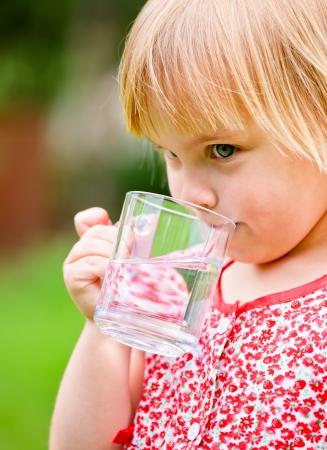 purified water: Lindo poco de agua potable de la muchacha al aire libre