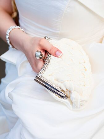 Bride holding white pouch close-up photo
