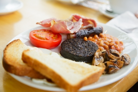 bacon baked beans: Plate with Full Scottish breakfast containing  toasts, fried eggs, baked beans, grilled black pudding, sausage, tomato,  mushrooms and bacon Stock Photo