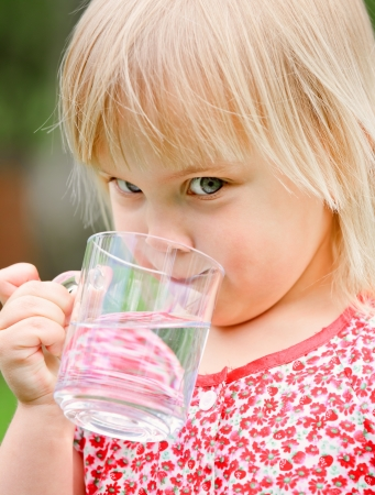 health drink: Cute little girl drinking water outdoors