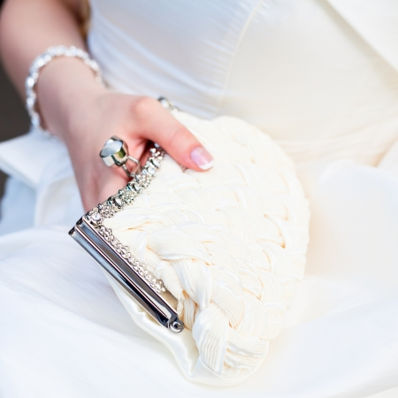 Bride holding white pouch close-up