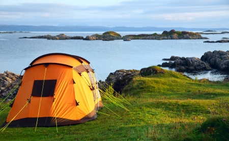 camping equipment: Camping tent on an ocean shore in a morning light