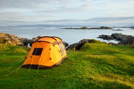 camp: Orange camping tent on a shore in a morning light