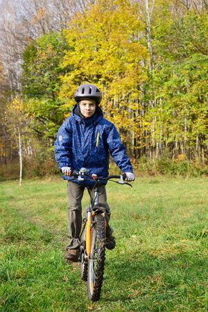 Kid cycling in autumn park photo