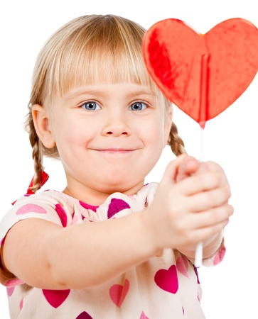 Cute little girl showing big red heart shaped lolly pop candy photo