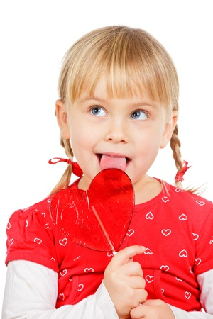 licking in isolated: Cute little girl licking big red heart shaped lolly pop candy