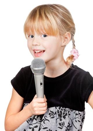 Canto linda niña que sostiene el micrófono en el fondo blanco