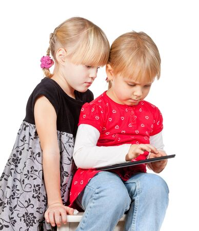 Two serious girls playing with a touch pad photo