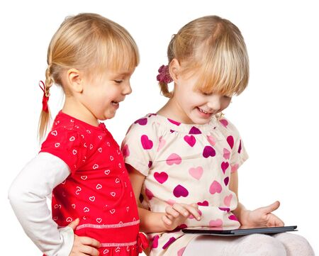 Two happy girls playing with a touch pad photo