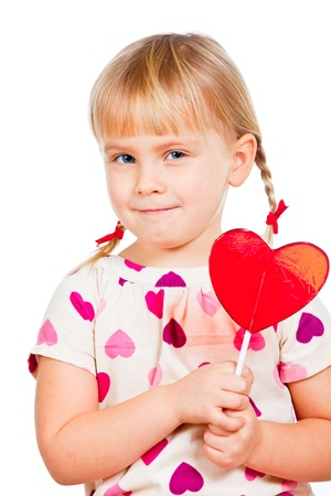 Cute little girl holding big red heart shaped lolly pop candy photo