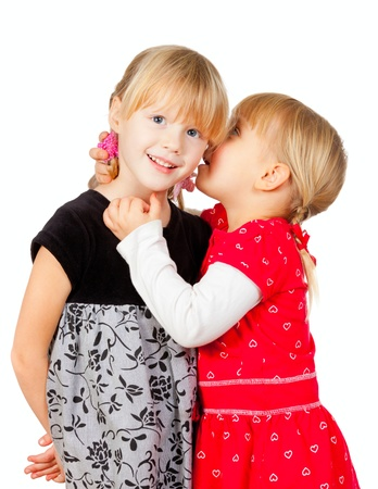 blab: Portrait of little girl  telling a secret to her friend over a white background