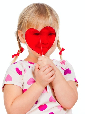 Cute little girl looking through big red heart shaped lolly pop candy photo