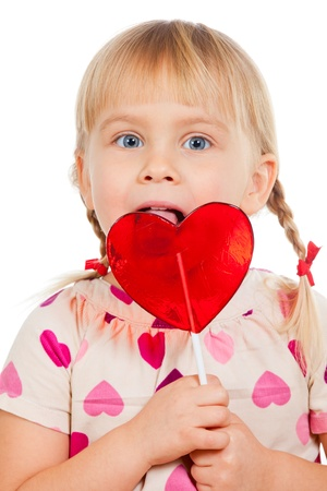 Cute little girl licking big red heart shaped lolly pop candy photo