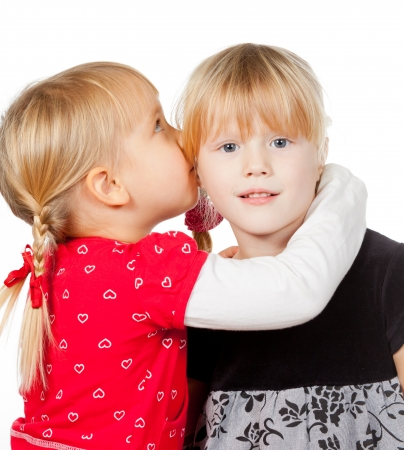 rumor: Portrait of little girl  telling a secret to her friend over a white background
